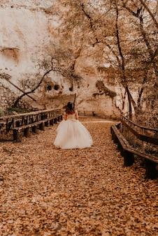 Sposa donna in abito da sposa bianco con trucco acconciatura e corona in testa cammina attraverso la foresta di autunno su foglie arancioni cadute