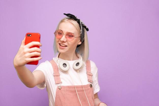 Donna in abiti luminosi e cuffie alla moda fa selfie e sorrisi