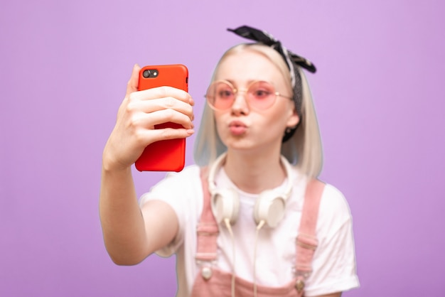 La donna in vetri rosa luminosi prende selfie sullo smartphone con la faccia buffa