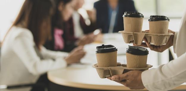 La donna porta i bicchieri di caffè da asporto in ufficio durante un gruppo di dipendenti, colleghi seduti e lavorano alla scrivania e poi salutano e felici con gentilezza. concetto di lavoro di squadra.