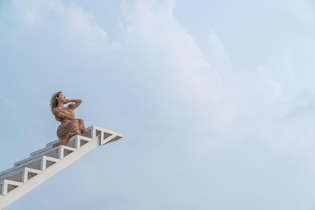 Donna in abito marrone seduto sulla scala.