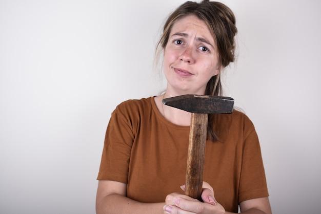 Donna in maglietta marrone, azienda martello, isolato. concetto di ristrutturazione casa