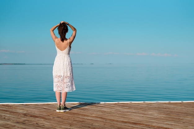 Donna castana in vestito bianco che sta su un pilastro di legno con le mani sulla sua testa che esamina l'orizzonte di mare, spazio della copia