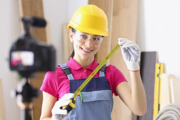 Il blogger costruttore di donna dice alla fotocamera come eseguire correttamente le misurazioni durante la riparazione