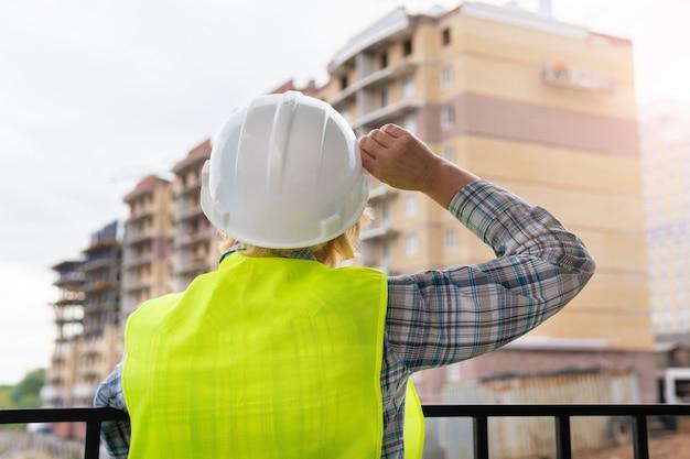 Una donna muratrice in un cantiere ispeziona un edificio