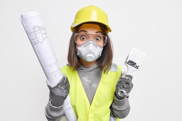 La donna costruttore o ingegnere lavora sul layout della stanza tiene brueprint e il pennello indossa l'uniforme da lavoro e l'attrezzatura di sicurezza occupata con la costruzione