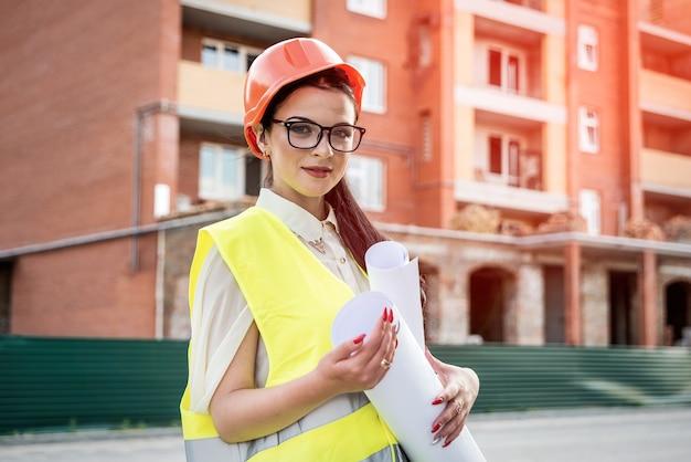 Donna in casco da costruttore e giubbotto che tiene in mano rotoli di progetti