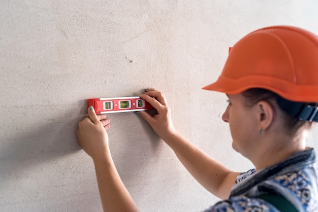 Muratore della donna che misura la parete dallo strumento del livello dell'acqua