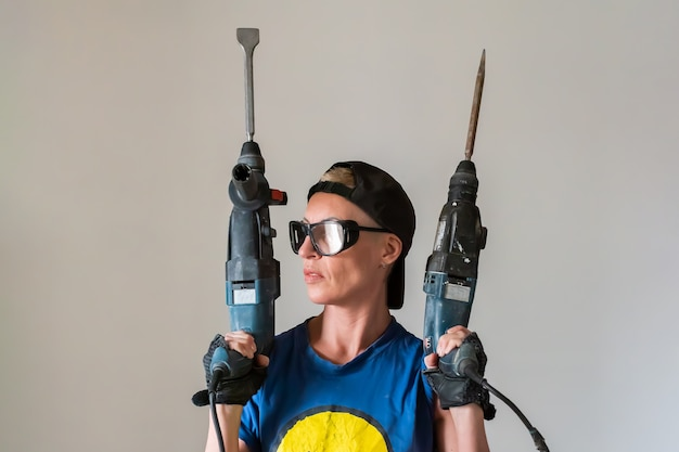 Costruttore di donna con un trapano in mano per qualsiasi scopo.