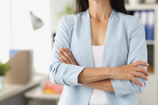 La donna in vestito blu di affari che sta con il suo primo piano ha attraversato le braccia