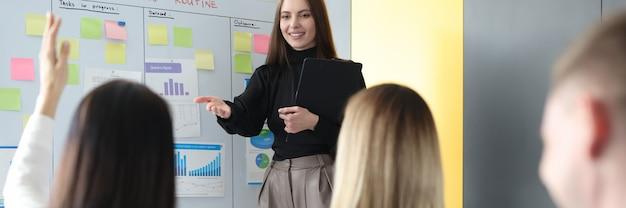 Istruttore di affari della donna che sta vicino alla lavagna e che fa la domanda all'ascoltatore