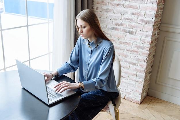 La signora di affari della donna utilizza il computer portatile al tavolo mentre era seduto