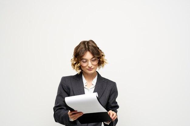 Donna in tailleur finanze documenti di lavoro occhiali acconciatura.