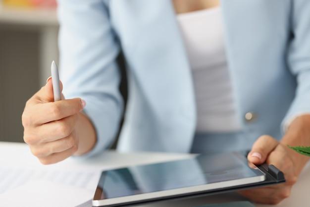 Donna in giacca e cravatta che tiene tablet digitale e stilo nelle sue mani primo piano
