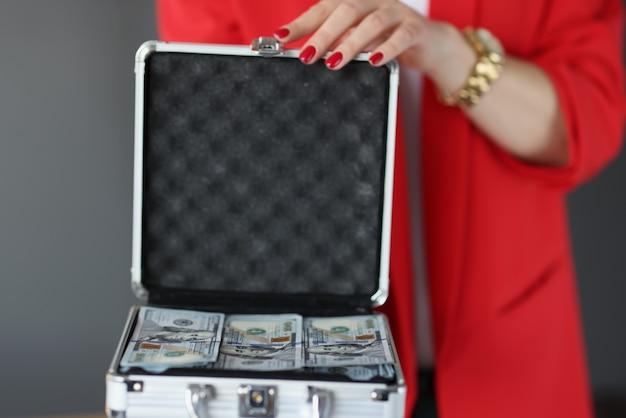 La donna in tailleur tiene la valigia piena di soldi soldi veloci online concept