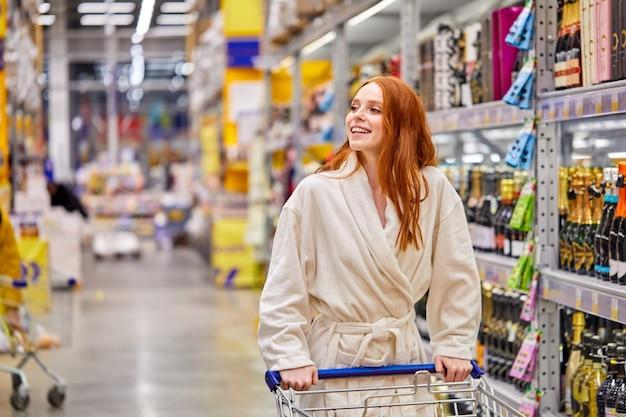 Donna che compra alcolici nel negozio, chossing per le vacanze, shopping da sola indossando accappatoio