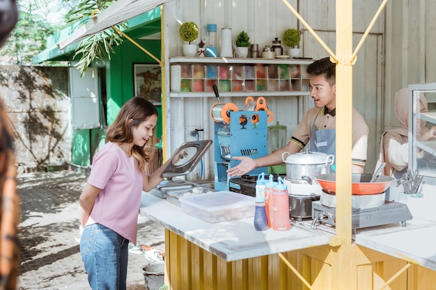 Donna che compra cibo al piccolo stallo alimentare. venditore di cibo di strada asiatico