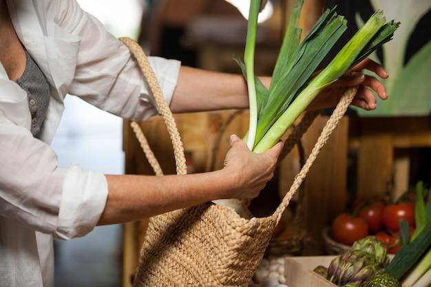 Donna che compra verdura a foglia verde nella sezione organica
