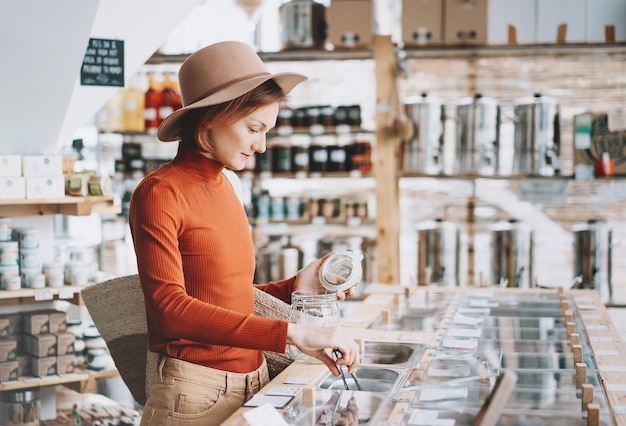 Donna che acquista prodotti locali in un negozio di alimentari senza plastica a zero rifiuti