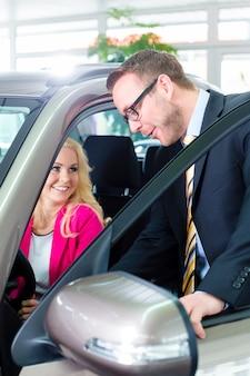 Donna che compra nuova automobile nel concessionario auto