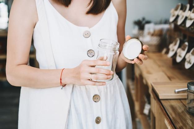 Donna che compra in un negozio di alimentari senza plastica ragazza con sacchetto di cotone riutilizzabile in un negozio a zero rifiuti waste