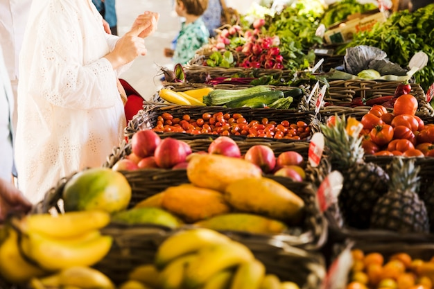 Donna che compra verdura e frutta al mercato degli agricoltori