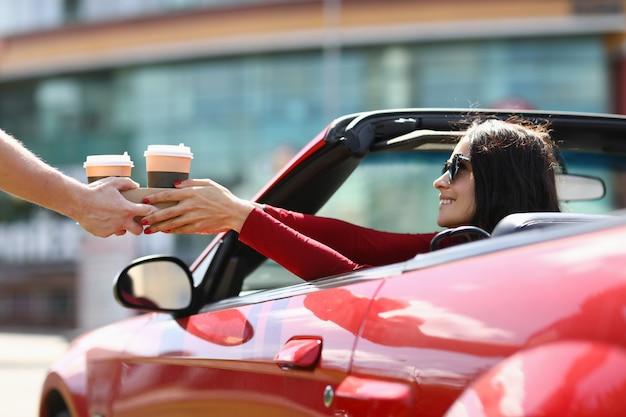 La donna in cabriolet raccoglie le bevande calde da un corriere. concetto di consegna di cibi e bevande