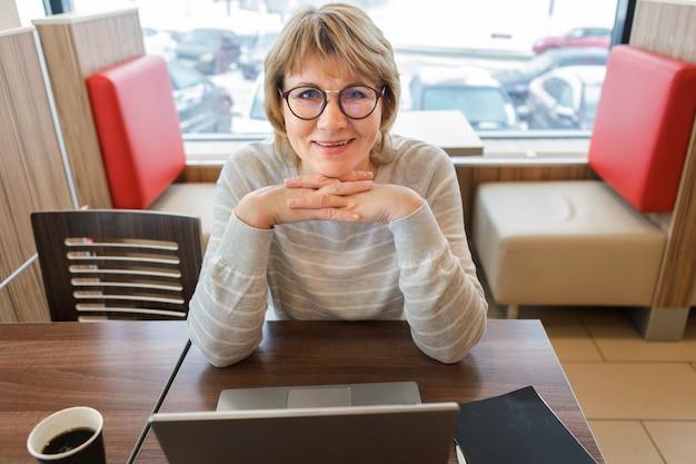 Una donna in un bar che lavora su un laptop. il concetto di business e lavoro a distanza.