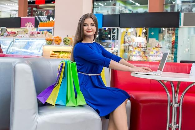 Donna in caffetteria con borse della spesa e laptop