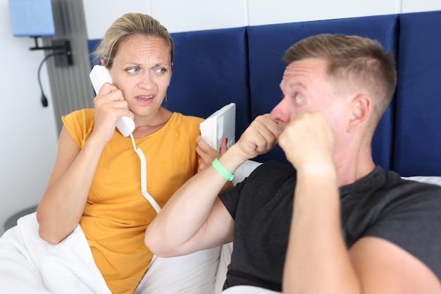 La donna chiama il medico dalla camera d'albergo per l'uomo con problemi agli occhi concetto di assicurazione medica di viaggio