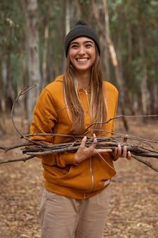 Donna in campeggio e raccolta di legna
