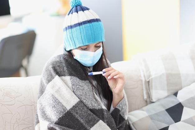 Donna in protezione e mascherina medica protettiva che esamina termometro