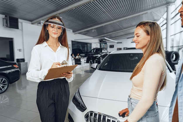 Concessionario di auto donna consulenza acquirenti che indossano visiera medica. coronavirus concetto di requisiti di lavoro