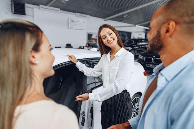 Rivenditore di auto donna che spiega agli acquirenti le caratteristiche della loro nuova auto