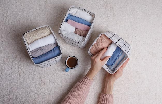 La donna piega con cura i vestiti e li mette in ceste e scatole. minimalismo in stile scandinavo.