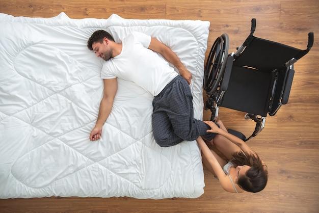 La donna che si prende cura dell'uomo disabile sul letto. vista dall'alto