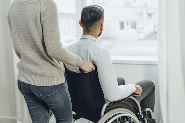 Donna che si prende cura di uomo disabile in sedia a rotelle a casa si chiuda