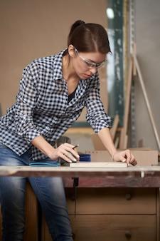 Carpentiere donna con metro a nastro e lavagna in officina