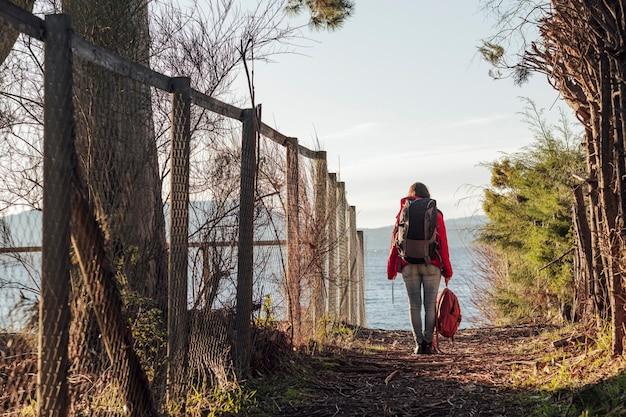 Donna che porta uno zaino mentre si cammina su una strada in mezzo alla foresta