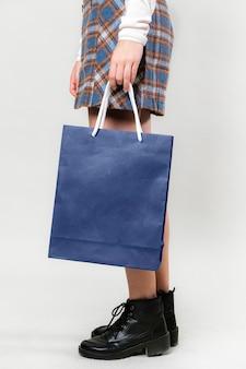 Donna che porta una borsa della spesa blu