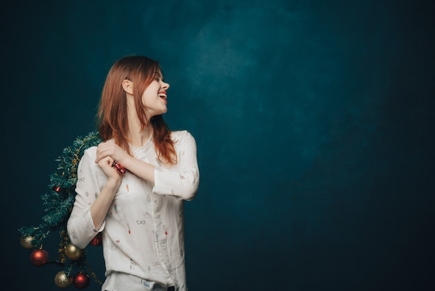 Donna che porta albero di natale decorato