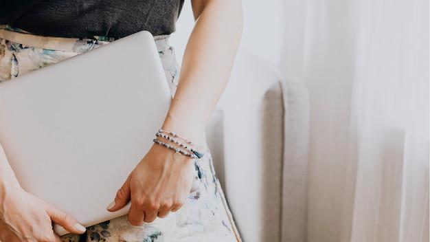 Donna che porta un laptop in una stanza