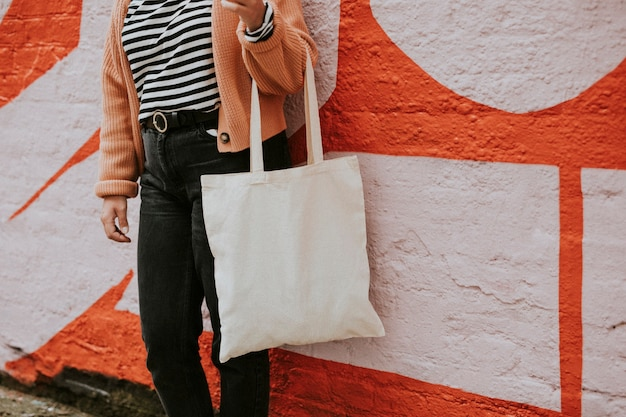 Donna che trasporta una borsa tote riutilizzabile in tela bianca