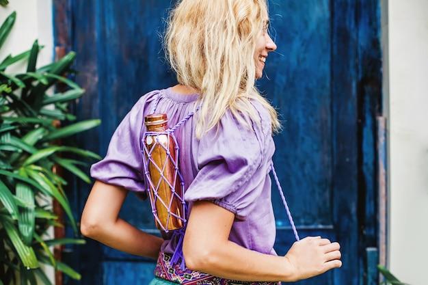 Donna che trasporta una bottiglia di rame riutilizzabile con manici indossabili