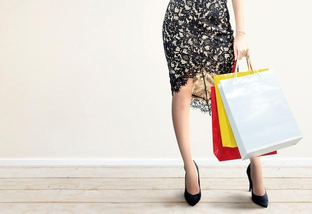La donna che porta le borse della spesa in piedi con il muro bianco