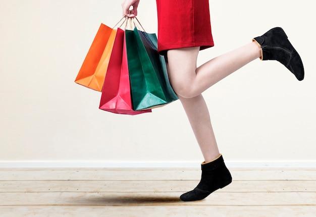 La donna che porta le borse della spesa con muro bianco
