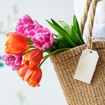 Donna che porta i tulipani in una borsa di vimini
