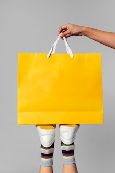 Donna che porta una borsa della spesa gialla