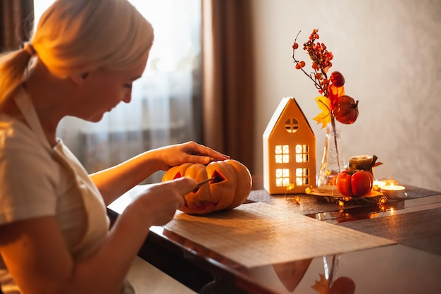 Una donna intaglia una zucca per halloween in una stanza con decorazioni autunnali e una lampada. casa accogliente e preparati per halloween