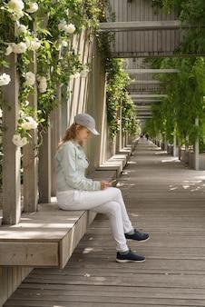 Donna in abiti casual seduta su una panca di legno con rose bianche su un muro all'aperto